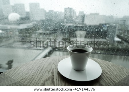 A cup of coffee at front and City view through a window on a rainy day - stock photo