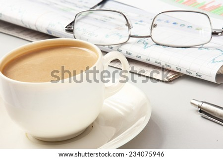 a cup of coffee, glasses and a pen on papers - stock photo