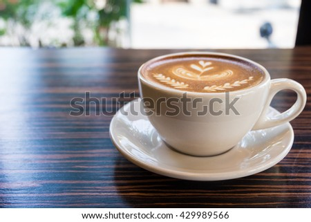 A cup of coffee latte with flower, leaf and heart shape art - stock photo