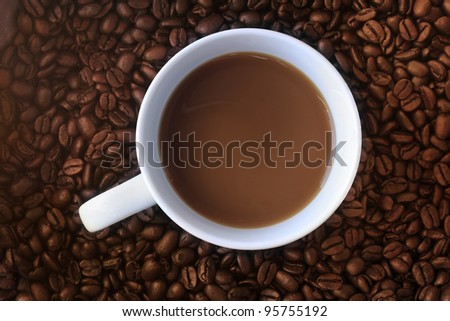 a cup of coffee on a background of dark roast beans - stock photo