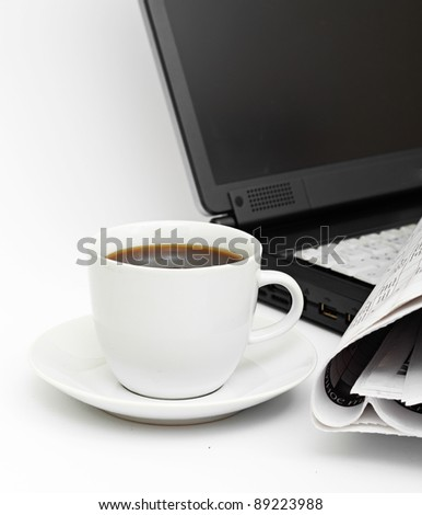 A cup of coffee on a laptop on white background
