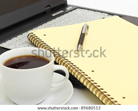 A cup of coffee on a laptop on white background - stock photo