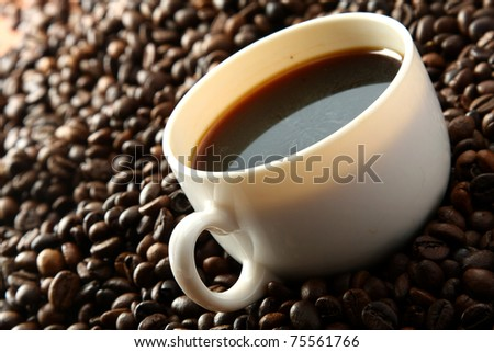 A cup of coffee on coffee beans, closeup - stock photo