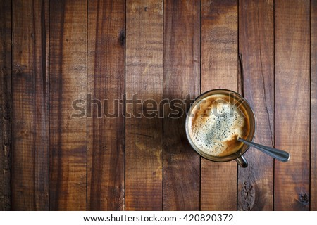 A cup of coffee on the background of the wooden table. Coffee on wooden background. Space for text. Top view. - stock photo
