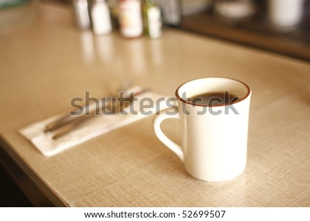 A cup of coffee on the counter at a diner.