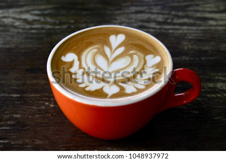 A cup of coffee on the table and the coffee latte art of blooming flower.