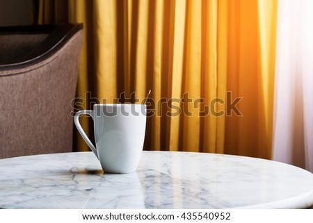 A cup of coffee on the table at the morning light - stock photo