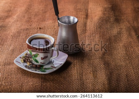 A cup of coffee on the table. Coffee brewed in Arabic. Coffee and Turk for brewing coffee on the table. - stock photo