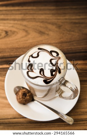 A cup of coffee on wooden background - stock photo