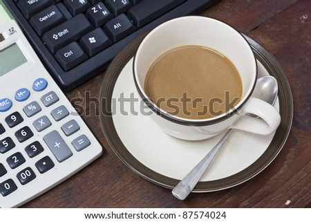 A cup of coffee on wooden desk top