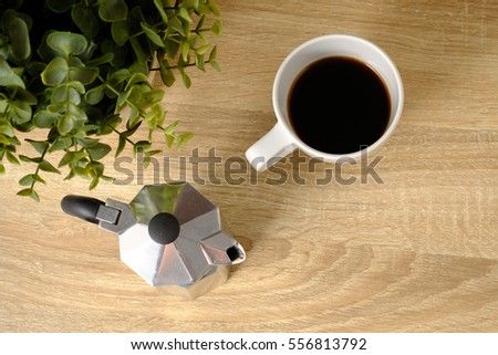 A Cup of coffee on wooden table with moka pot in morning time, top view