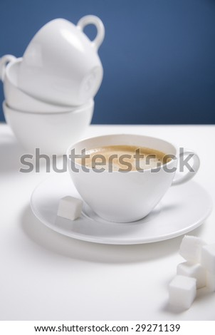 A cup of coffee surrounded by sugar cubes and dirty cups in the background. - stock photo