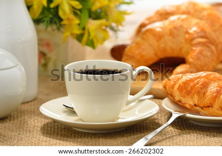 A cup of coffee with bread and croissant