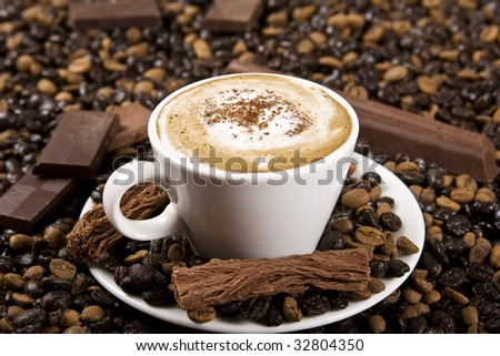 A cup of coffee with chocolate and coffee beans. - stock photo