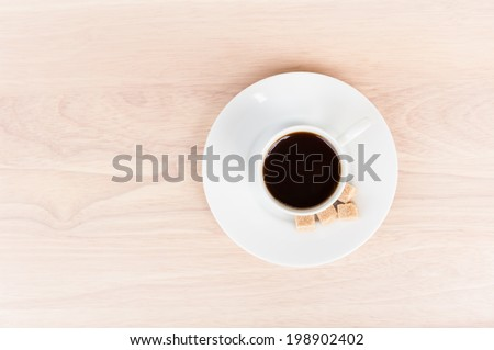 a cup of coffee with four square sugar