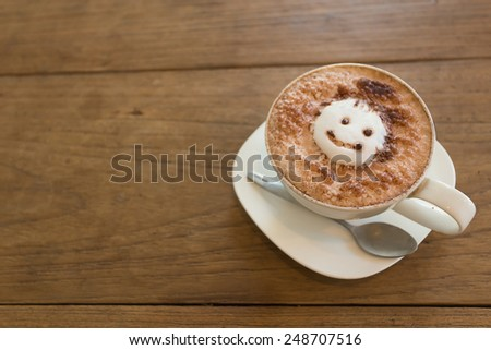 A cup of coffee with smile milk foam on the wooden background - stock photo