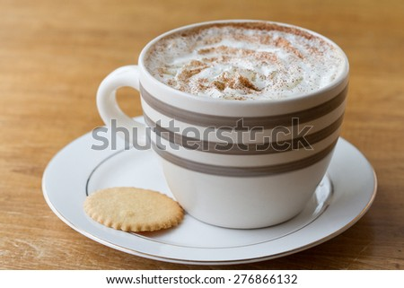 A cup of coffee with whipped cream in an oversize mug - stock photo