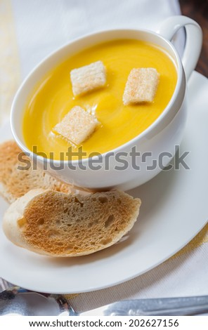 A cup of creamy pumpkin soup with croutons and lightly toasted baguette slices