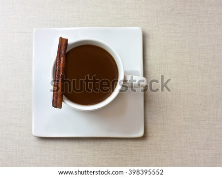 A cup of dark hot chocolate with a cinnamon stick on a burlap background texture, with a place for text - stock photo
