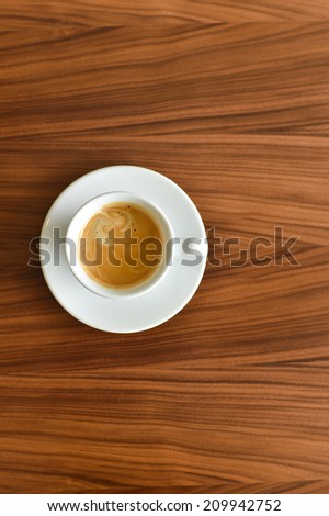 A cup of espresso coffee on the wooden table - stock photo