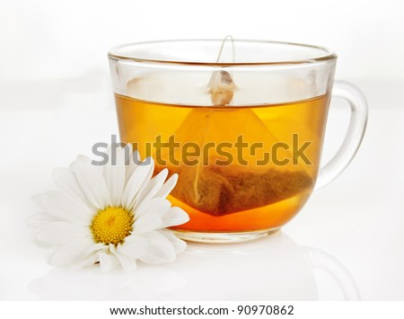 a cup of fragrant green tea with a triangular teabag - stock photo