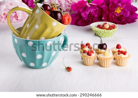 A cup of fresh berries and mini tartlets with custard and wild strawberry. - stock photo