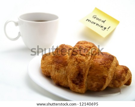 A cup of fresh coffee, a delicious croissant and a yellow note with this text: 'Good morning!' - stock photo