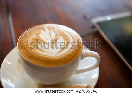 A cup of fresh hot coffee on white plate and smartphone on wooden background - stock photo