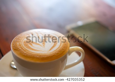 A cup of fresh hot coffee on white plate and smartphone on wooden background with sunlight in the morning - stock photo