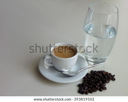 a cup of fresh tasty coffee with coffee beans and a glass of water - stock photo