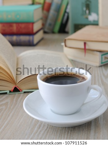a cup of freshly brewed coffee on a table with books - stock photo