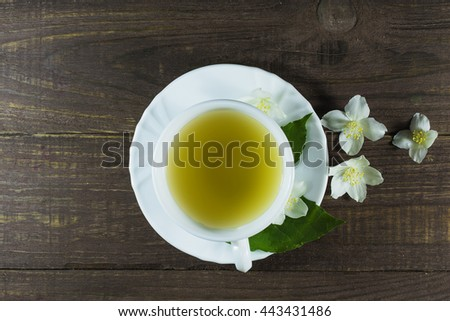 A cup of green jasmine tea standing in the center with white jasmine flowers and green leafs on a wooden background. top view - stock photo