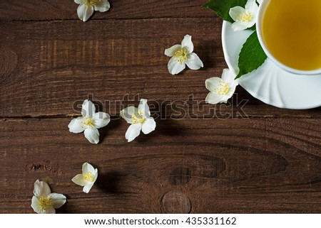 A cup of green jasmine tea standing in the corner with white jasmine flowers and green leafs on a wooden background. top view. with copy space - stock photo