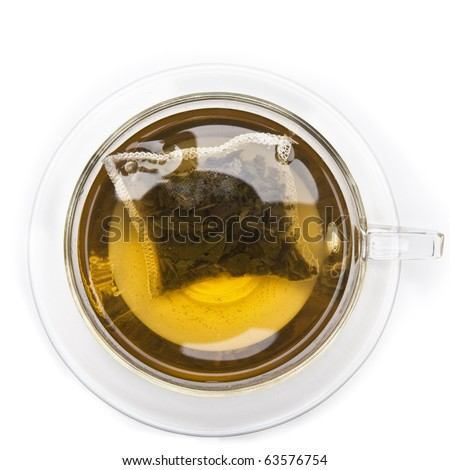 A cup of green tea with tea bag from above, on white background - stock photo