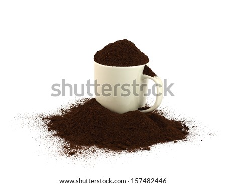 A cup of ground coffee with many of them spread around. White background./Too much coffee. - stock photo