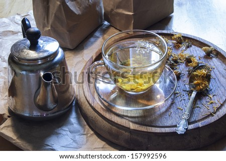 A cup of herbal tea. Near kettle, tea spoon and dried marigold flowers on a wooden board.
