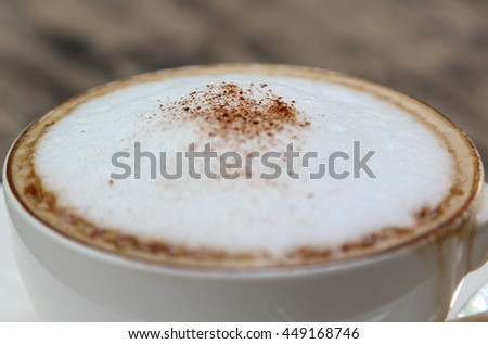 A cup of hot cappuccino on table.