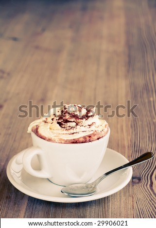 A cup of hot chocolate with cream on a wooden textured table - stock photo