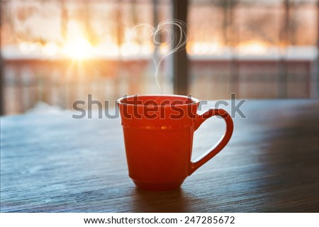 a cup of hot coffee on a rustic table against the morning rising sun  - stock photo