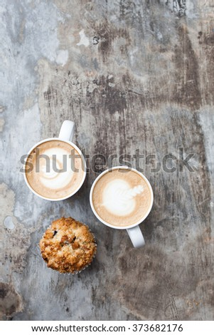 A Cup of Hot Latte Art Coffee with Muffin on Grey Vintage table - stock photo