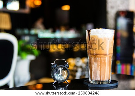 A cup of ice cappuccino on the table with coffee shop background  - stock photo