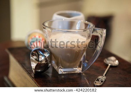a cup of iced coffee and a spoon for ice cream and milk jug on the table - stock photo