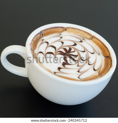 a cup of latte art on black background