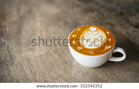 a cup of latte coffee on vintage table background. - stock photo