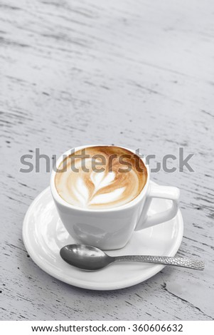 A Cup of latte coffee on white wood table - stock photo