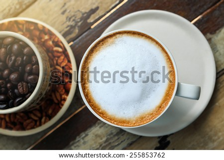 A cup of latte coffee on wood - stock photo