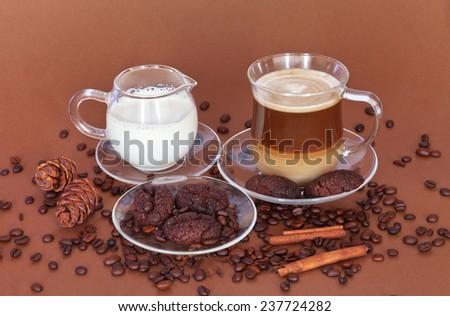 A cup of latte coffee with milk and cookies from the ground coffee with pine nuts and cinnamon. A good start to the day - stock photo