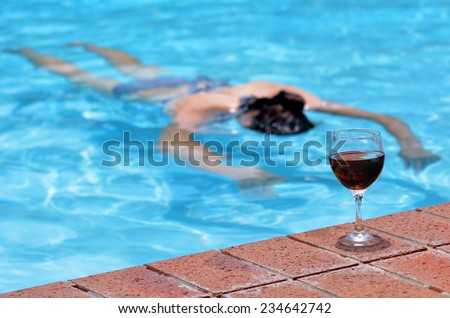 A cup of red wine on a pool side with drunk drowning person (woman) in a swimming pool at the background. Concept photo - stock photo