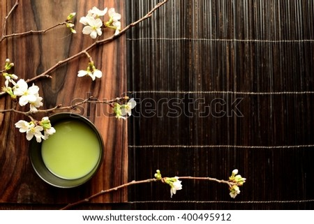 A cup of reen tea and cherry blossoms - stock photo
