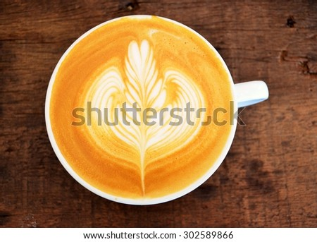 A cup of Rosetta Latte Art coffee on wood table - stock photo